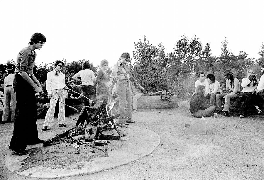 a few people gathered around the bonfire at the 1972 picnic